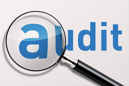 the word audit with a magnifing glass over the a